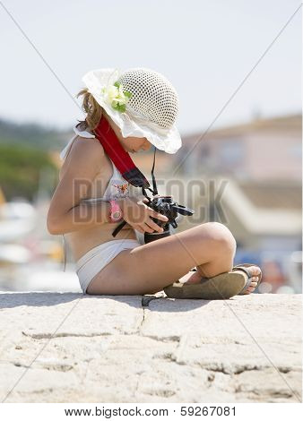 Young girl sits with her camera