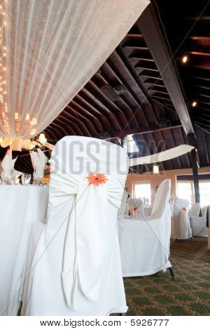 Wedding Venue With Covered Chairs And Ceiling Decoration