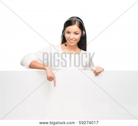 Young, confident and beautiful customer support operator with the blank billboard isolated on white