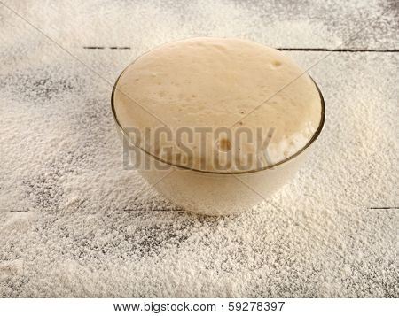 Rising Yeast Dough in glass bowl on wooden  table with wheat flour