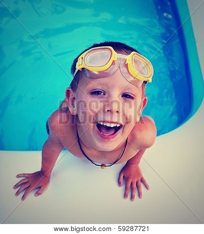a young boy swimming in a small pool done with a vintage retro instagram filter