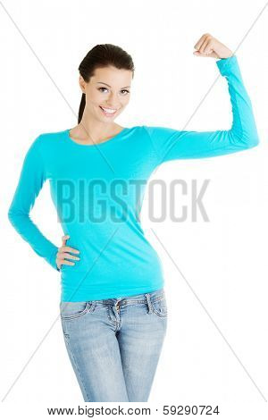 Young woman shows her biceps. She wears glasses and informal dress. Isolated on the white background.
