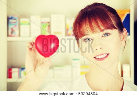 Woman in pharmacist uniform is standing in drugstore and showing red small heart, symbol of cardiology.