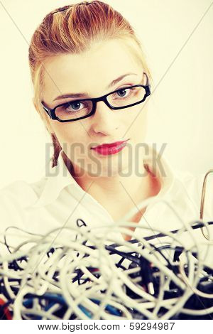 Young blond woman in black glasses and white shirt with cables and wires. Blond girl looking sceptically at computer parts.