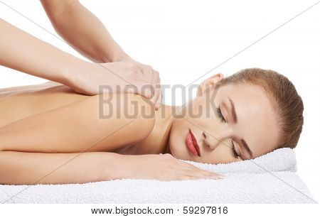 Beautiful caucasian woman lying and relaxing at spa saloon, having massage. Isolated on white.