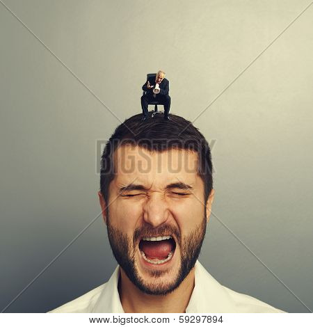 boss screaming at big businessman over dark background