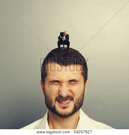 small angry boss screaming at big worker over grey background
