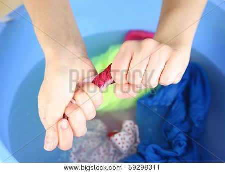 Hand washing in plastic bowl close-up
