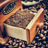 pic of wooden box from coffee mill  - Vintage stylized photo of coffee grinder and coffee beans close up - JPG