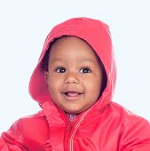 Adorable african baby with a beautiful smile and a red raincoat on a blue background