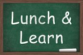 stock photo of ampersand  - Lunch and Learn Education written on a chalkboard with a piece of white chalk - JPG