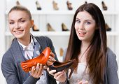 Salesperson offers heeled shoes for the female customer in the shopping center