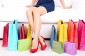 foto of pink shoes  - Female in red shoes sitting on sofa with shopping bags close up - JPG
