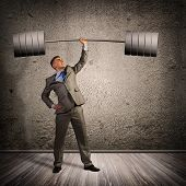 foto of barbell  - businessman holding a barbell with one hand - JPG