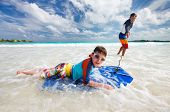foto of boogie board  - Father and son surfing on boogie boards - JPG