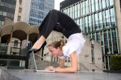 stock photo of contortion  - The model balances on one leg whilst on the phone - JPG
