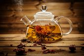 picture of teapot  - Glass teapot with blooming tea flower inside against wooden background - JPG