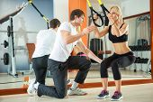 image of supervision  - Woman doing workout with fitness straps under supervision an personal trainer - JPG