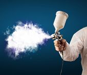 stock photo of airbrush  - Painter with airbrush gun and white magical smoke concept - JPG