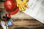 stock photo of muffs  - Personal Protective Equipment with house plans on floor - JPG