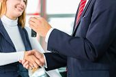 Seller or car salesman and customer in dealership, they shaking hands, hands over the car keys and s