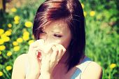 foto of blowing nose  - Young woman in summer dress standing on meadow during sunny day  and wiping her nose - JPG
