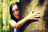 Young woman holding face next to tree trying to hear voice of nature. Girl standing with ear next to