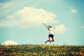 stock photo of cheers  - Happy woman jumping on blossom meadow - JPG