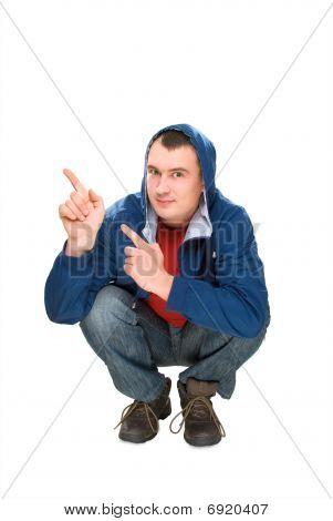 Feliz de los hombres en cuclillas y apuntando los dedos hacia arriba