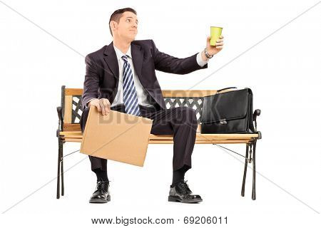Broke businessman holding a cup and blank banner isolated on white background