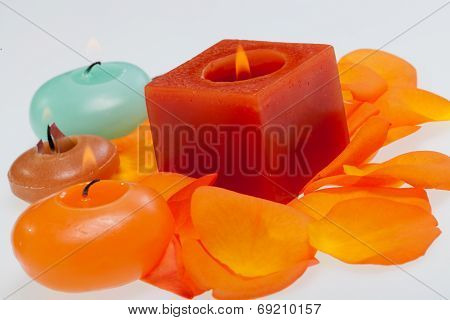 Spilt petals of the orange rose around the aromatic candle