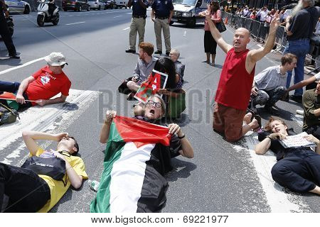 Activists supine on 2nd Ave with flags