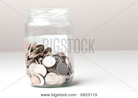Coins change quarters cents in a glass jar on a table