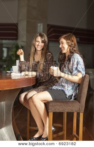 Two Young Women Drinking Coffee At A Bar