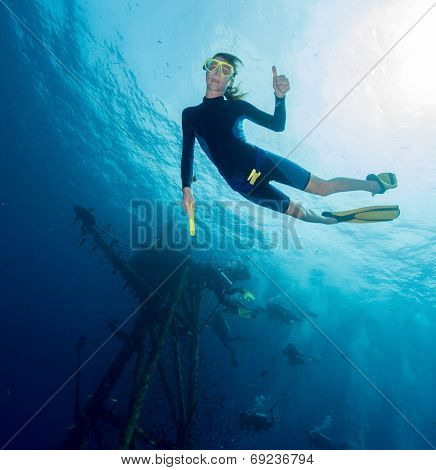 Free diver on depth with ship wreck on the background