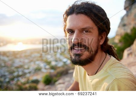 A smiling man with dreadlocks sitting on a mountain smiling at the camera with copyspace