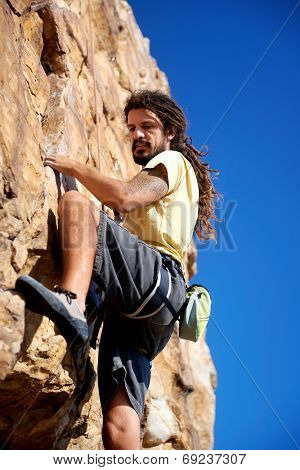 A rock climber finding a foothold on the steep mountain he's climbing