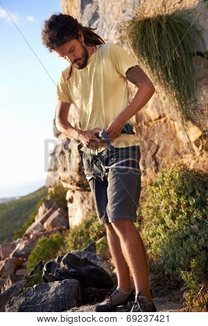 Man with dreadlocks putting on his harness to go rock climbing