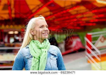 leisure, amusement park and people concept - smiling young woman in amusement park with carousel on the back