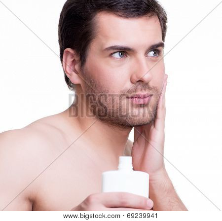 Young handsome man applying cream lotion on face - isolated on white.