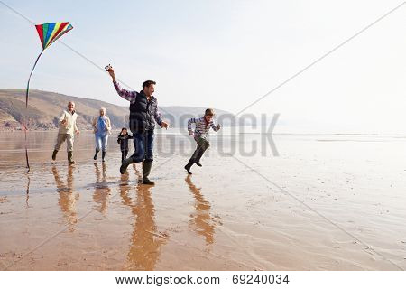 Multi Generation Family Flying Kite On Winter Beach