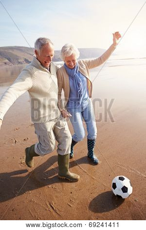 Senior Couple Playing Football On Winter Beach
