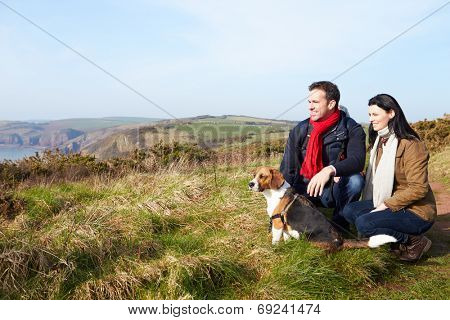 Couple With Dog Walking Along Coastal Path