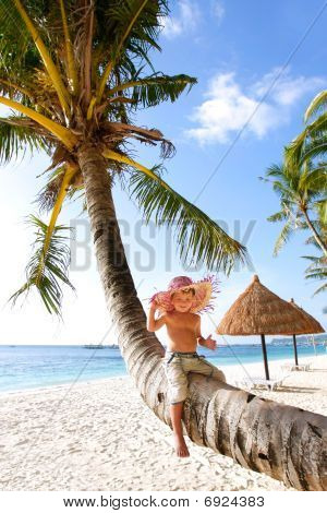 Happy Boy Sitting On Palm, Sand Beach Background