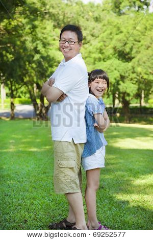 Father And Daughter Standing Back To Back