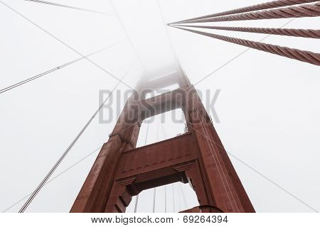 Golden Gate suspension bridge tower disappearing into San Francisco bay fog.