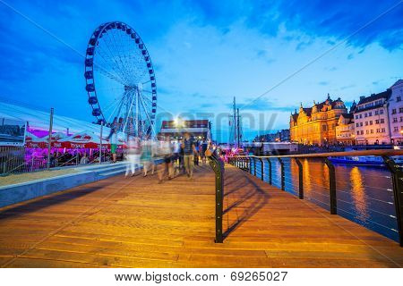 GDANSK, POLAND - 25 JULY 2014: Big wheel in Gdansk at night with promenade at Motlawa river. Gdansk is the historical capital of Polish Pomerania with medieval old town architecture.