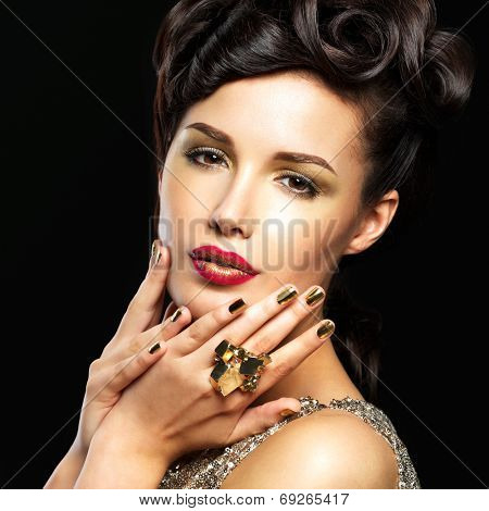 Beautiful  woman with golden nails and fashion makeup of eyes. Brunet girl model with style manicure on black background