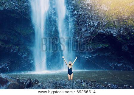 Woman enjoying pool at the base of large waterfall in Hawaii