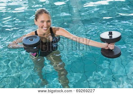 Fit blonde working out with foam dumbbells in swimming pool at the leisure centre